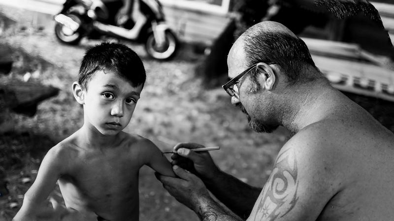мужчина делает временную татуировку ребенку